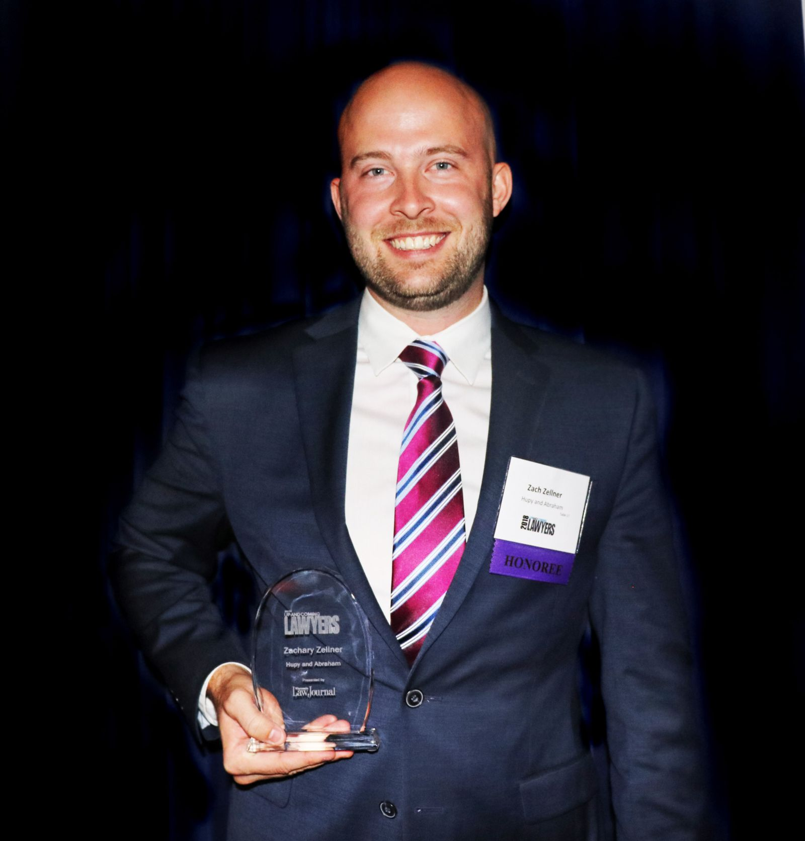 Attorney Zachary Zellner holding 2018 Up and Coming Lawyer award