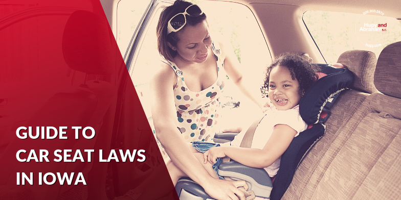 Young Mother Fastening Daughter Into Her Car Seat in Iowa
