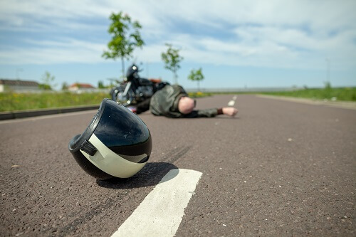 Motorcycle accident scene with rider with road rash injuries
