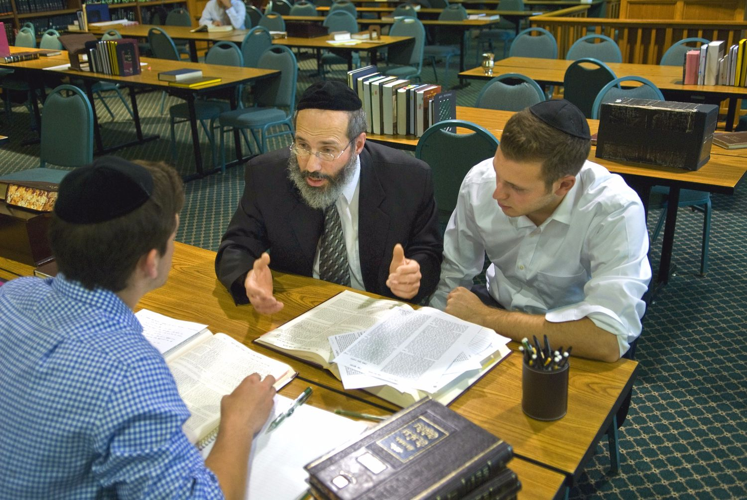 Rabbi sitting with two students