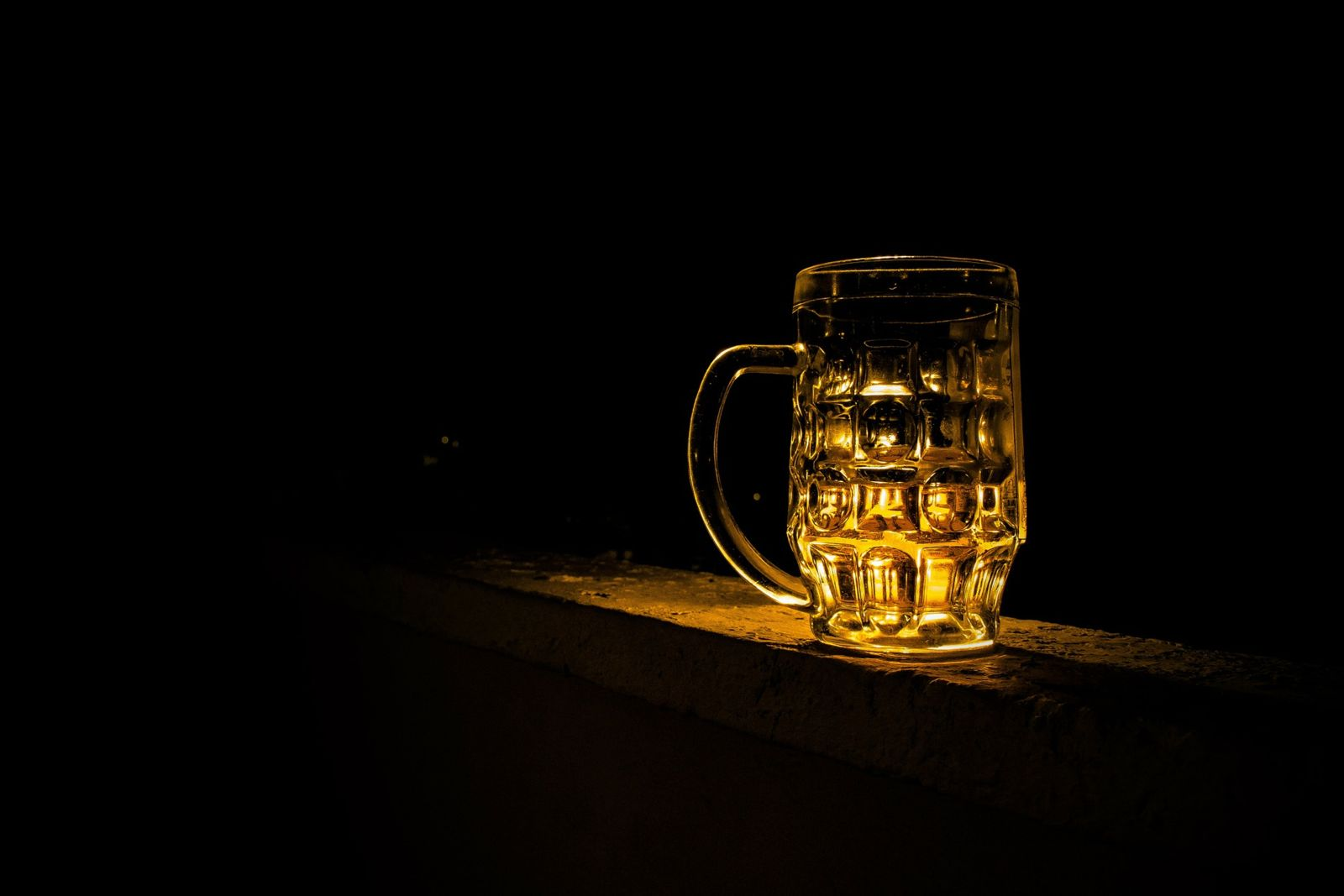 Glass of beer in dark setting