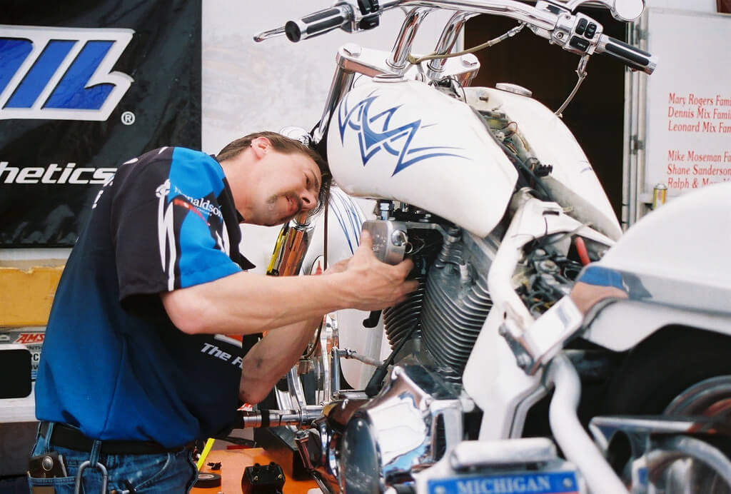 Motorcycle mechanic working on motorcycle with front end wobble