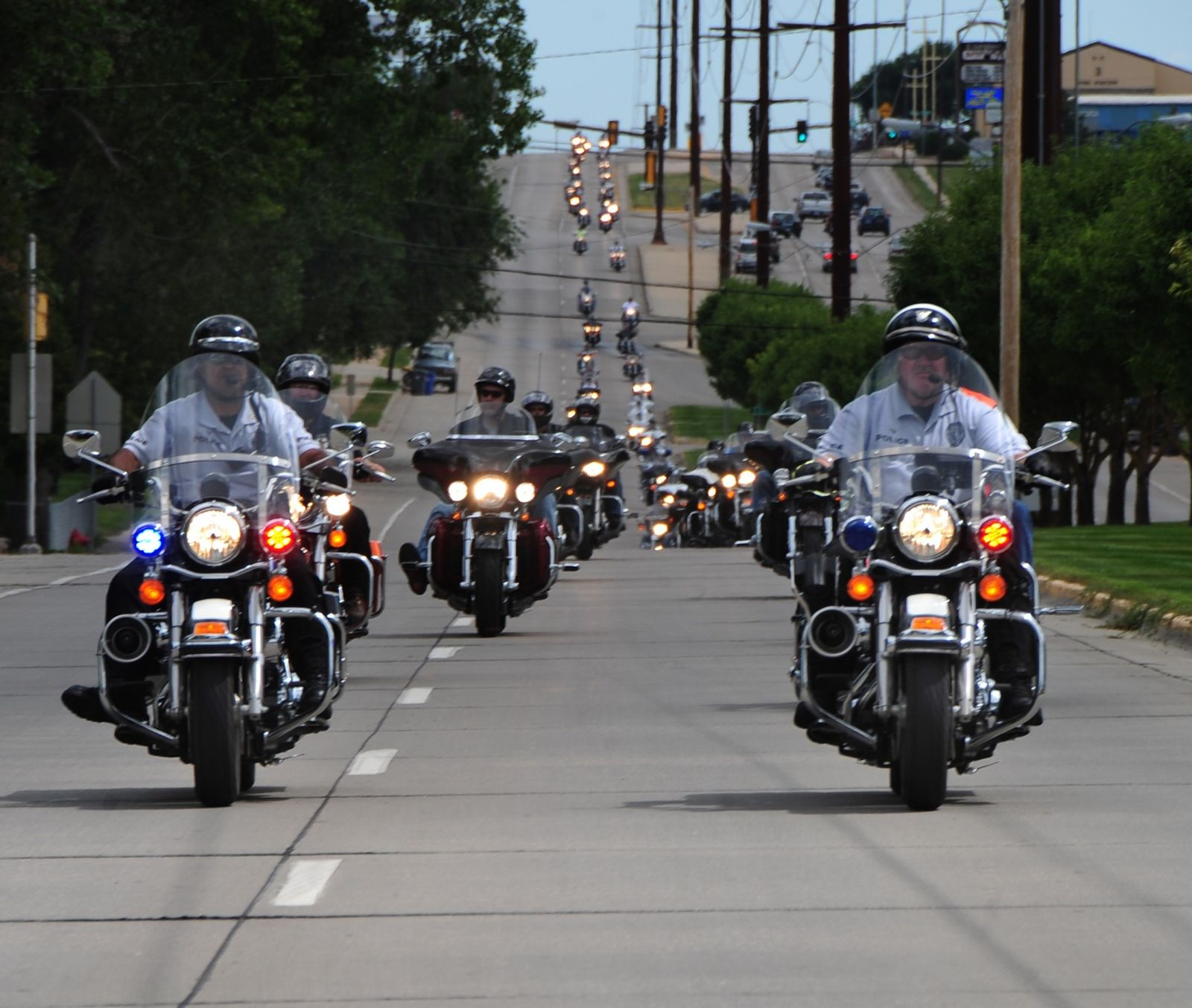 Large group of motorcycles in formation with Police motorcycles in front leading ride