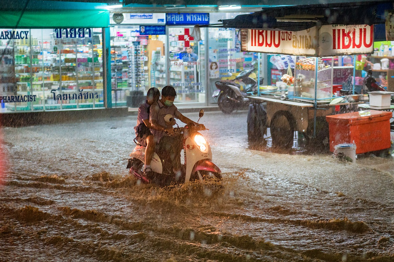 Moped with two people riding through water in rain