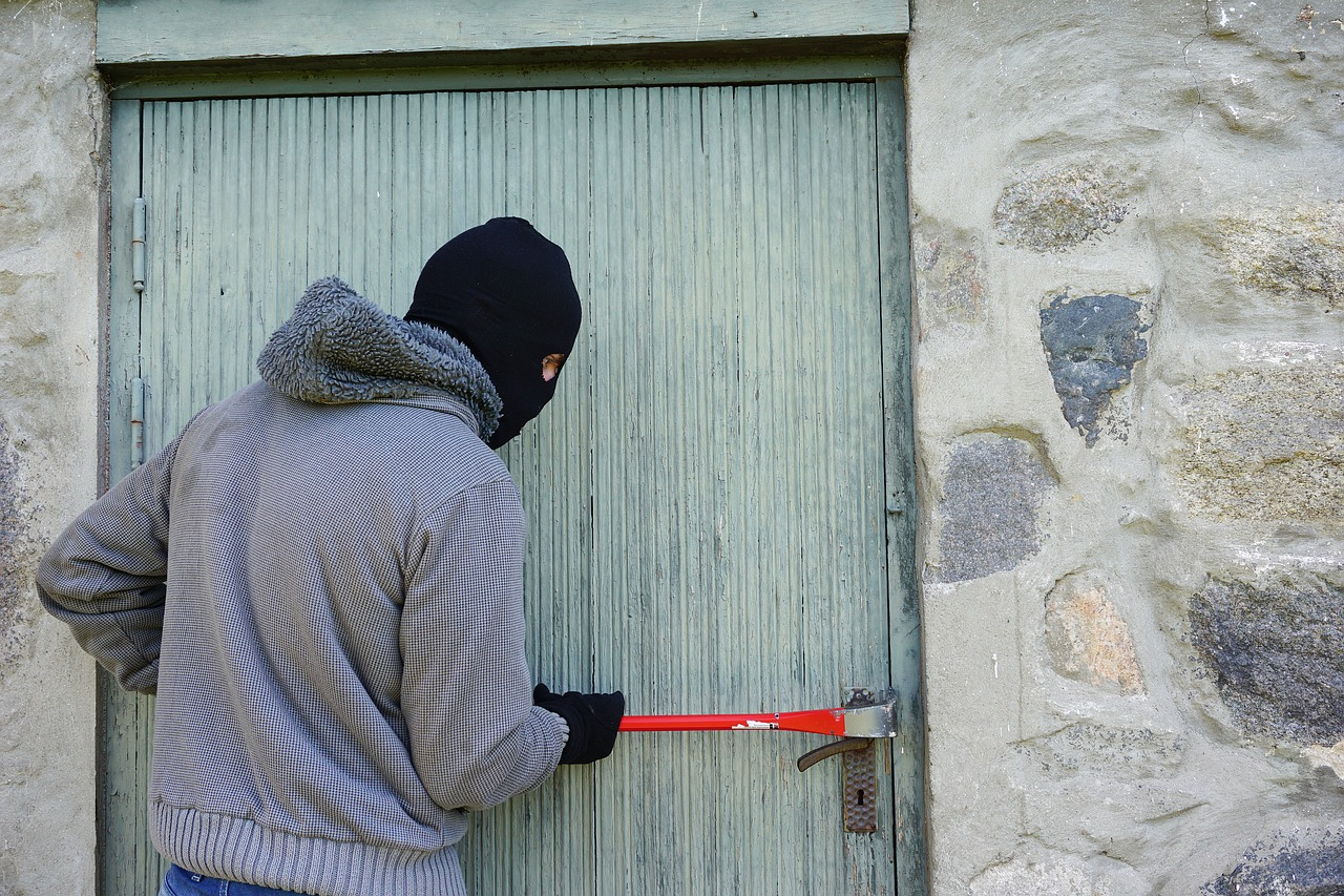 Man with mask breaking into a door with prybar