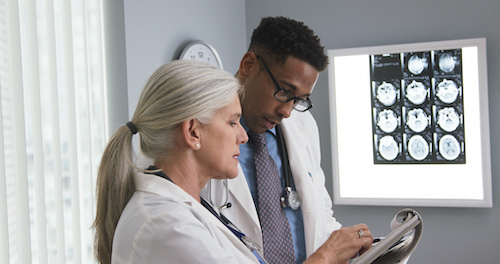 two doctors reviewing a brain injury scan