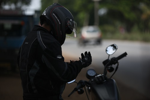 Motorcyclist putting gloves on on the highway
