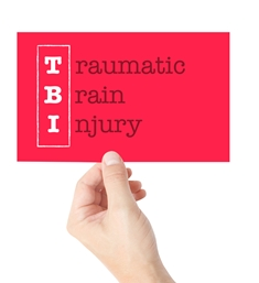Hand Holding a Traumatic Brain Injury Card