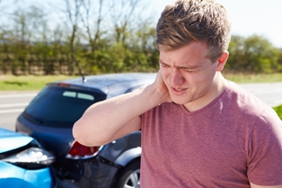 Passenger Holding His Neck in Pain After a Car Accident