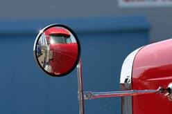 Red Semi-Truck's Front Mirror Showing Limited Rear Views