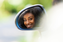 Teen Driver Looking in a Car's Mirror