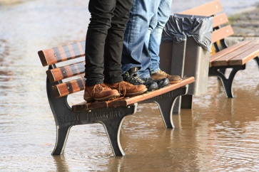 Two People Standing on a Bench Surrounded by Floodwater