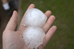 Hand Holding Two Large Pieces of Hail