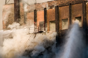 Smoke envelops a staircase while firefighters spray water into a burning building