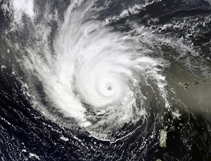 Black and white image of a hurricane passing over the terrain below