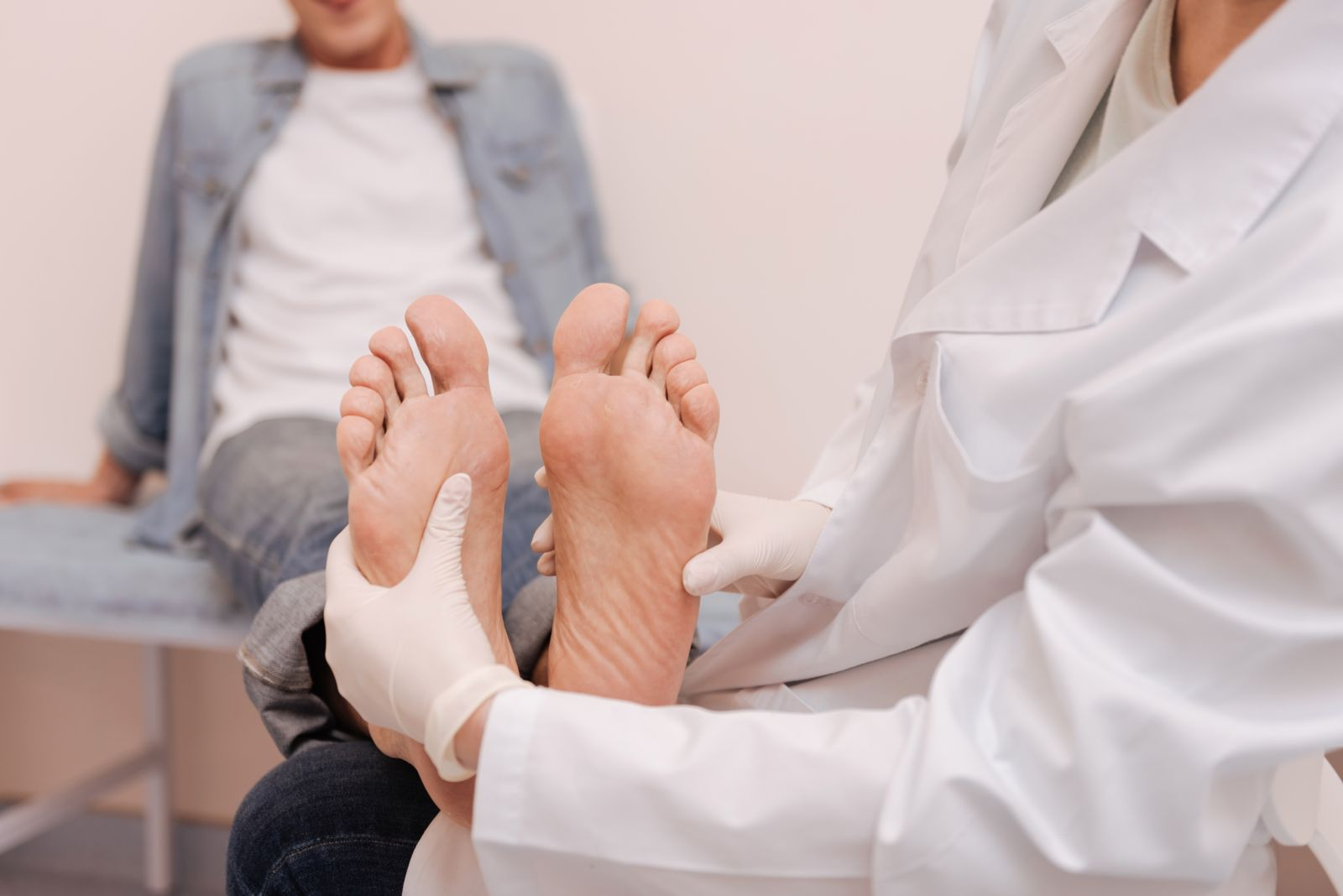 Doctor examining feet of patient
