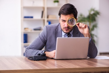 Investigator With a Magnifying Glass and Computer