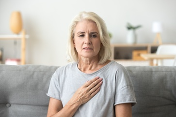 Woman Holding Her Hand Over Her Heart in Distress