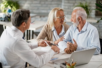 Senior couple asking an estate planning attorney questions during consultaion