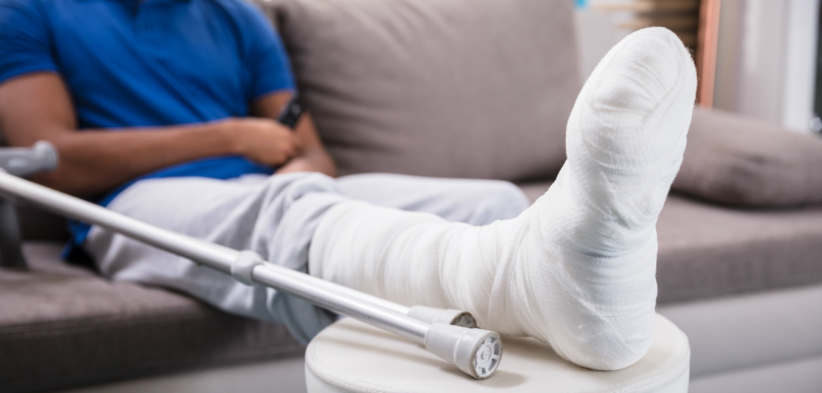 Man sitting on couch recovering from foot surgery