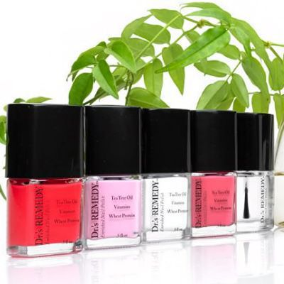Five bottles of nail polish in front of a plant.