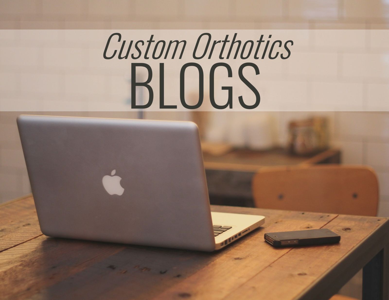 computer on a desk with the words: Custom Orthotics Blogs