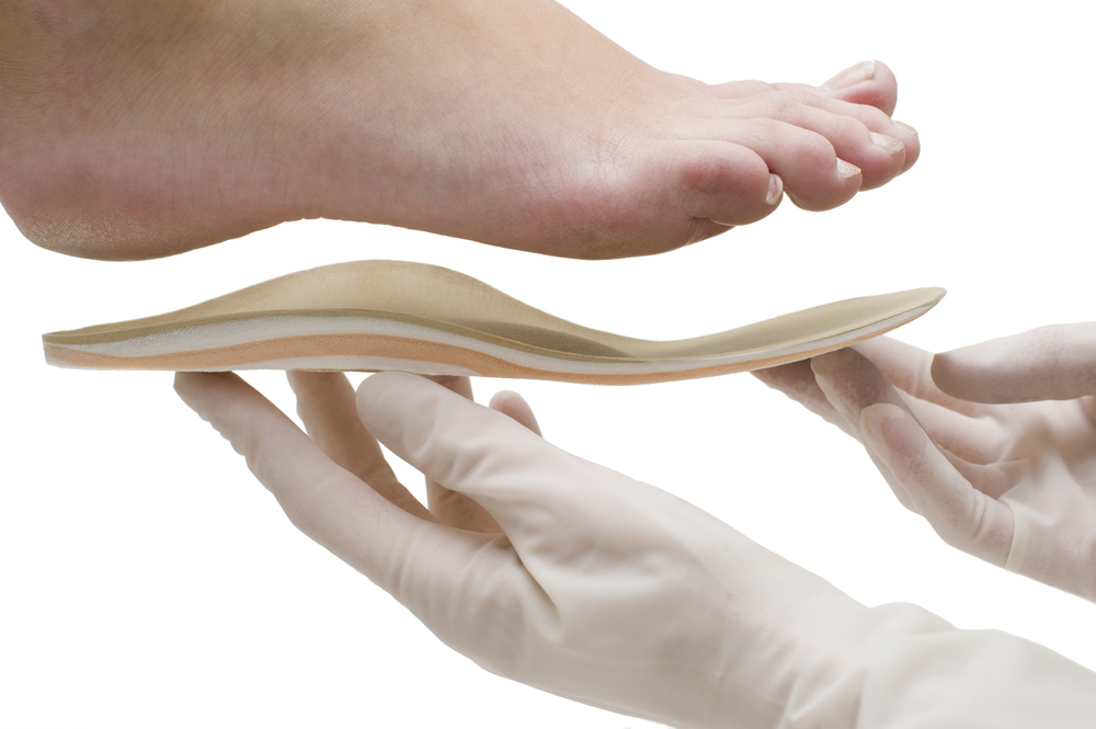Medically gloved hands holding an insert up to the bottom of a foot