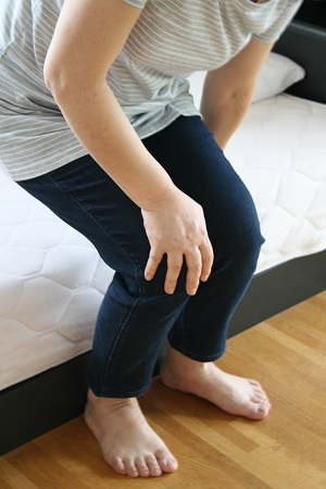 Woman getting out of bed with sore feet