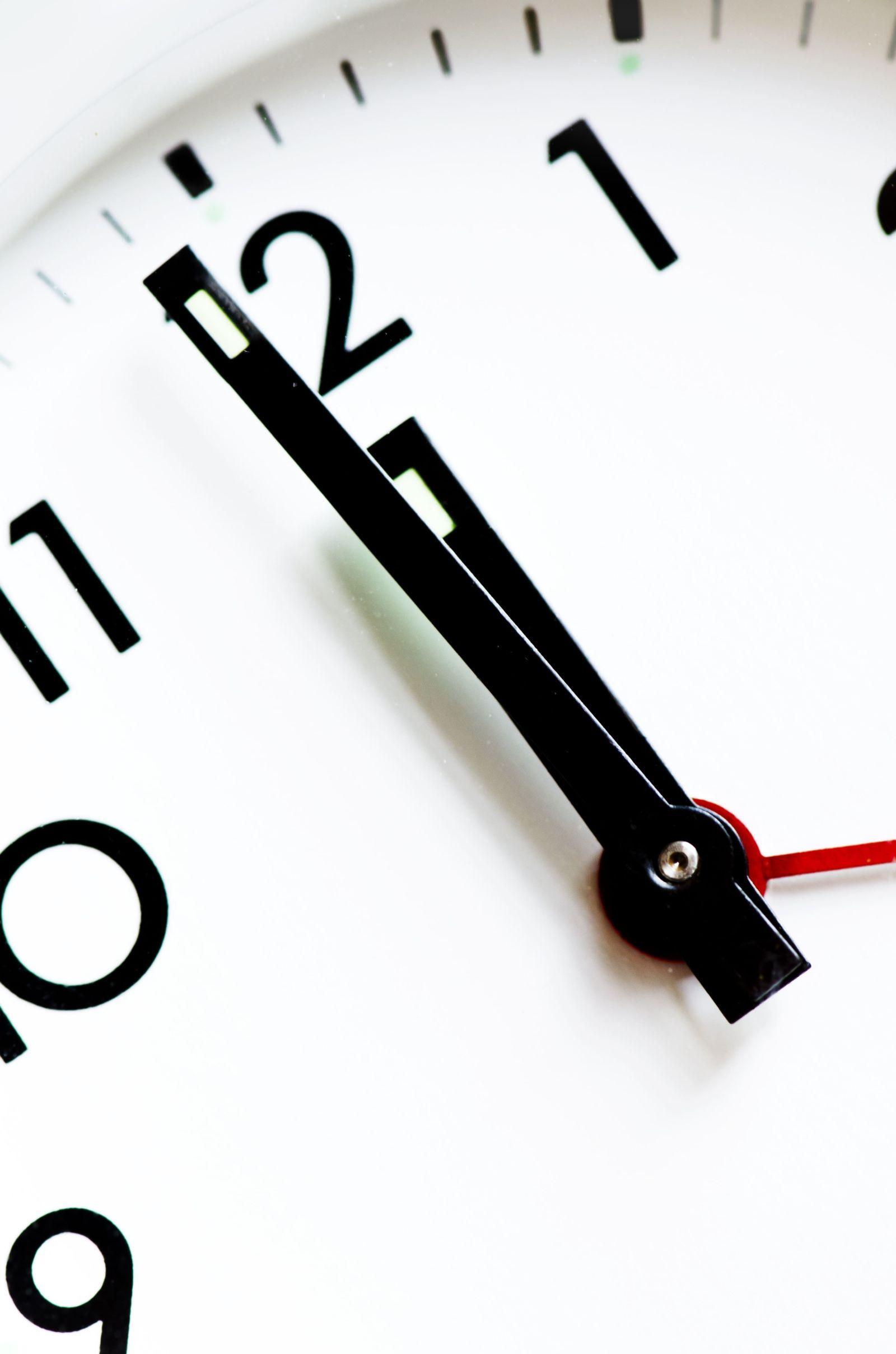 black and white analog clock showing 11:59
