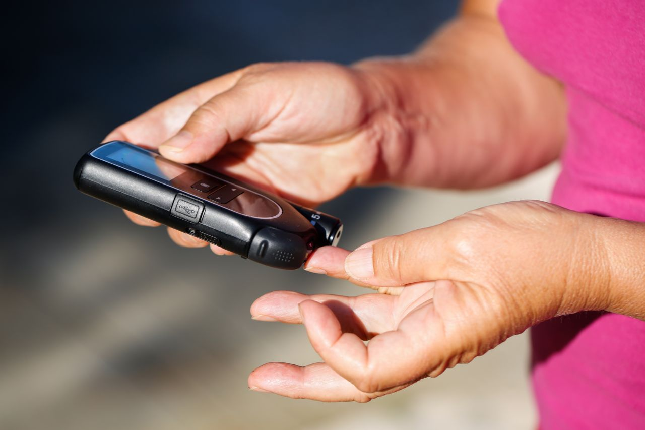 a person checking their blood sugar with a small device against their finger
