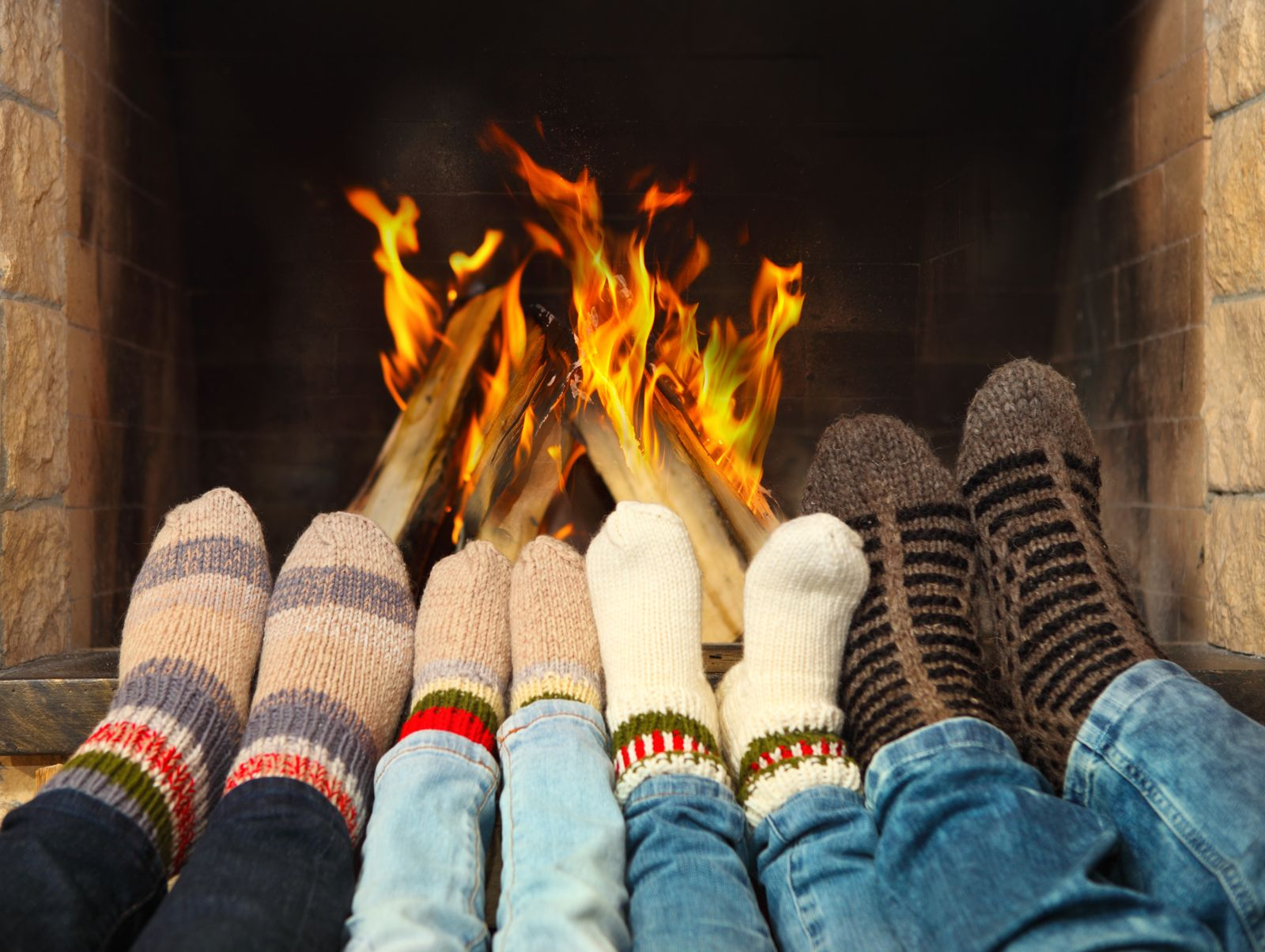 Four sets of feet wearing socks lined up in front of a fireplace