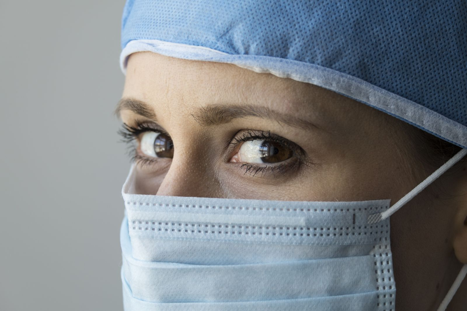 Female doctor wearing surgical mask and head covering