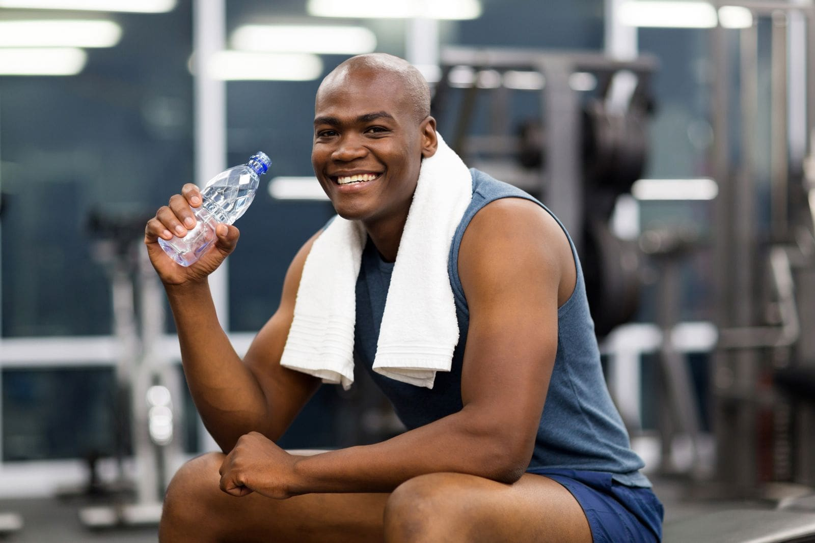 a man sitting in a gym wearing workout clothes and smiling while holding a water bottle