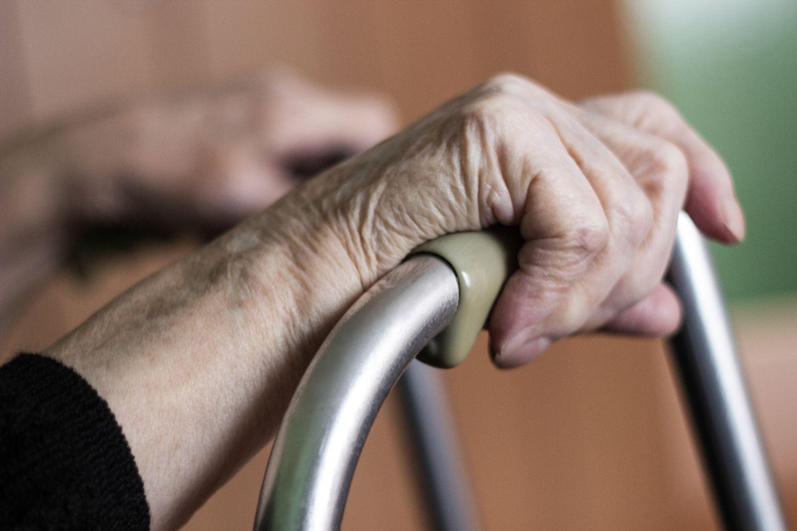 older woman's hands gripping a walker
