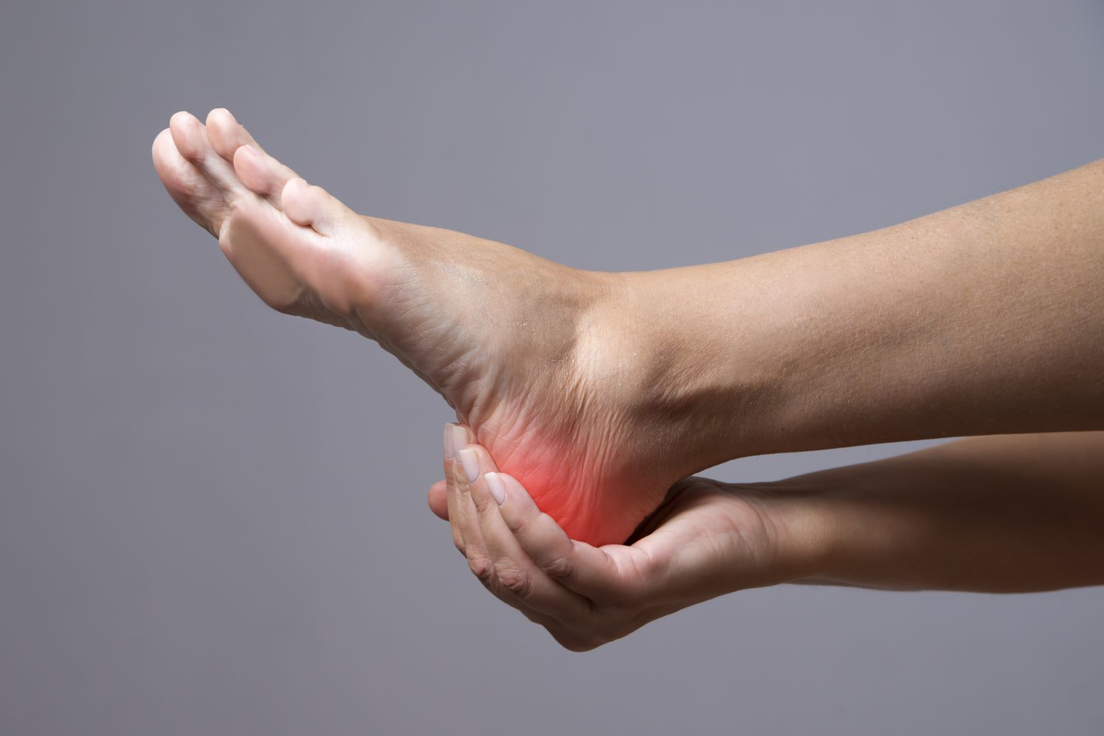 A foot with red heel and a person's hand holding the heel.