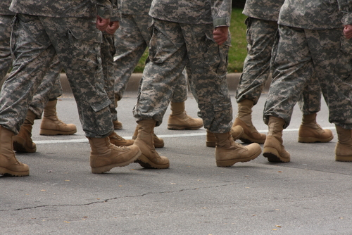 military people's feet marching in camo clothes with brown boots