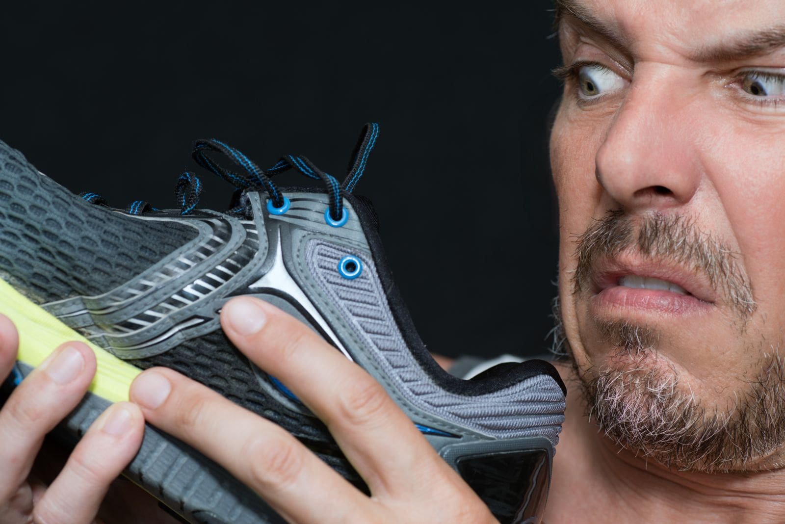 man looking at shoe with disgusted look on his face