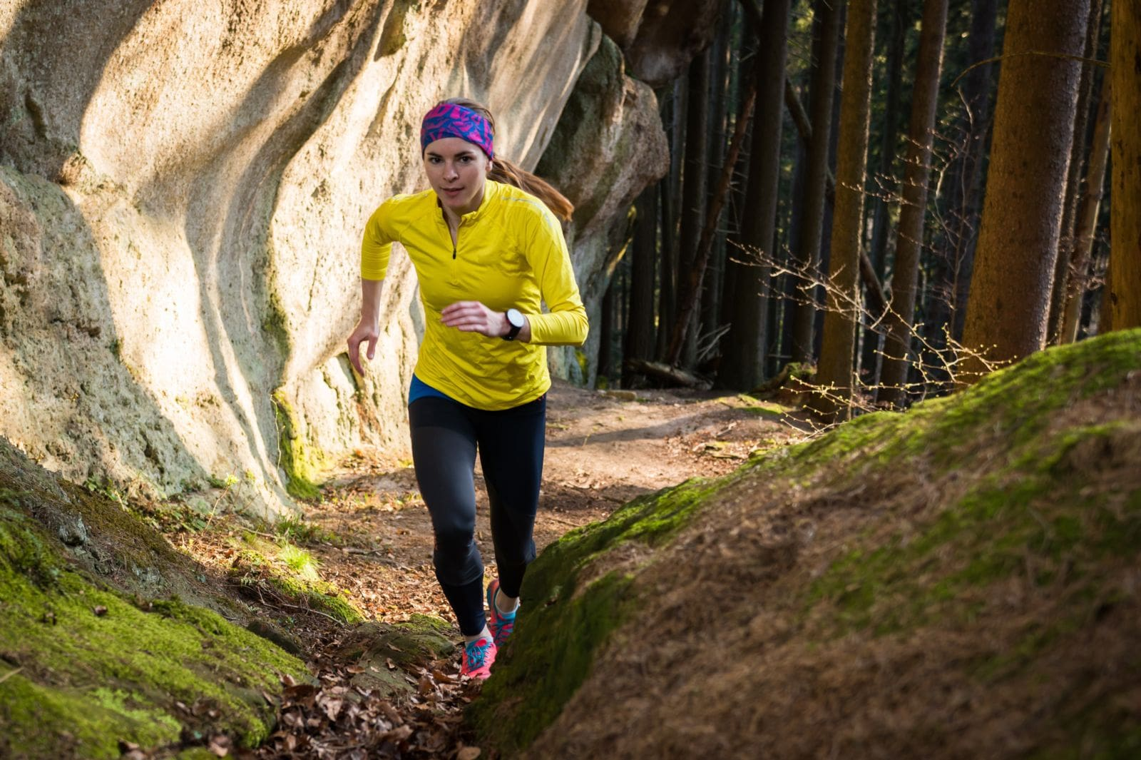 Girl running up a trail in a forest wearing yellow and black