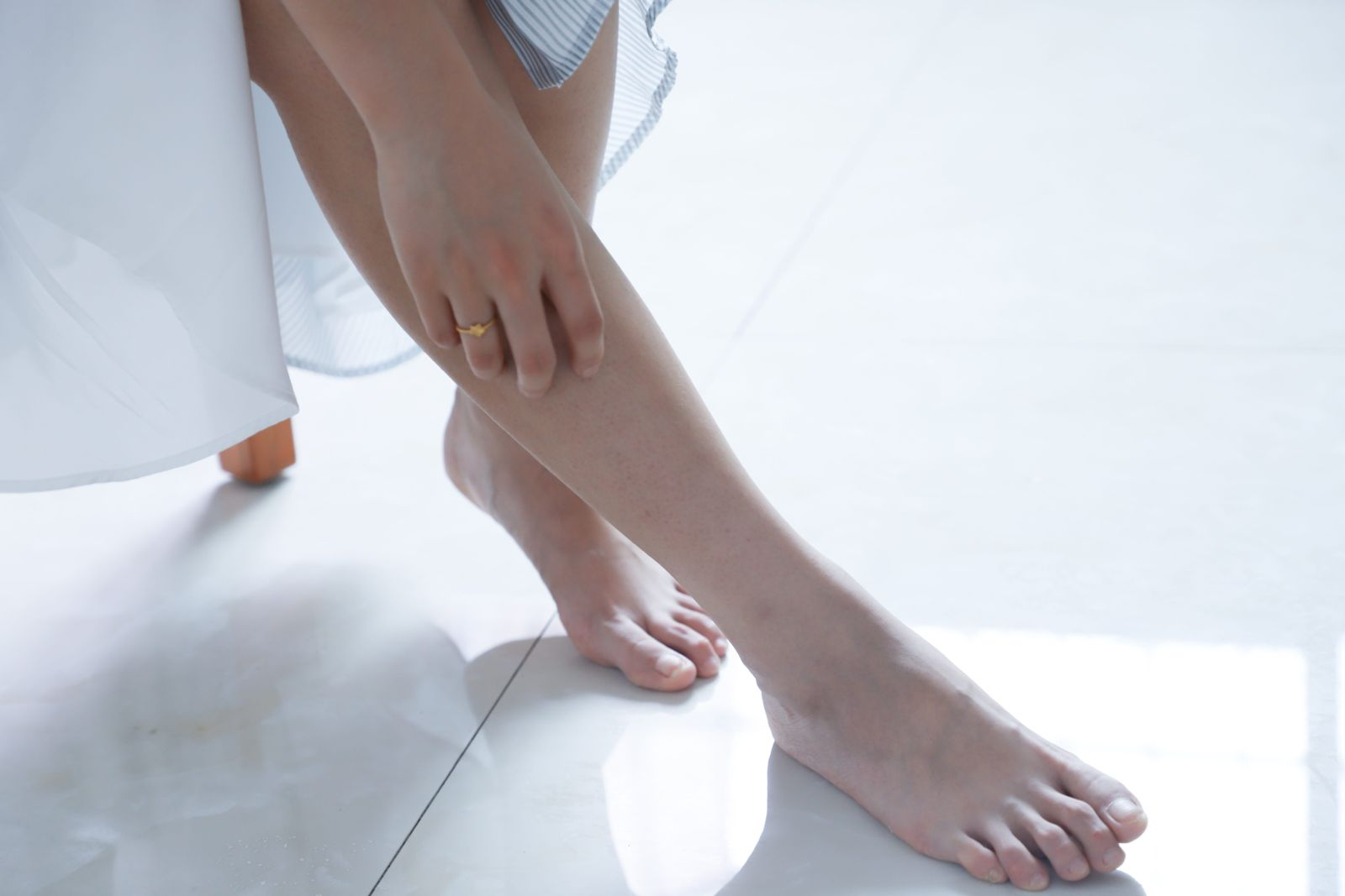 Woman reaching down to touch bare right foot on white floor