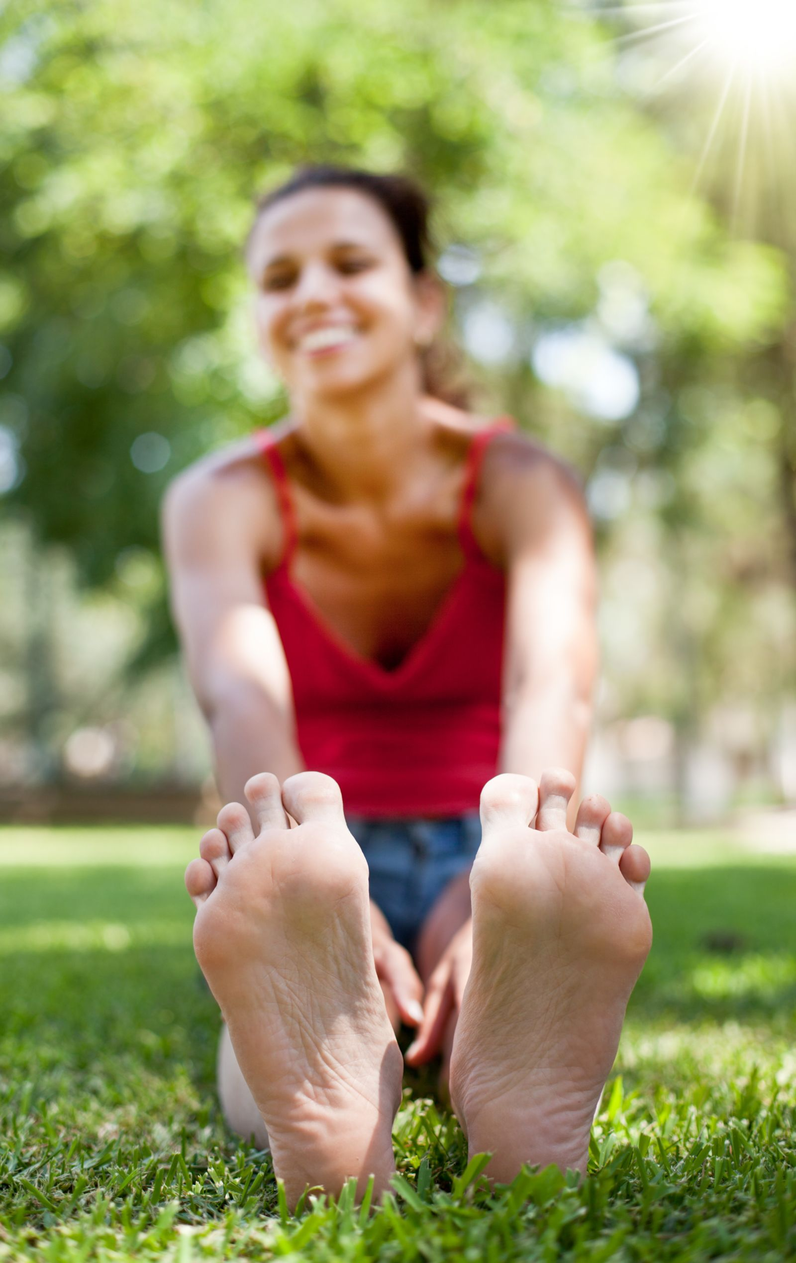 Picture of woman's feet outside stretching and smiling