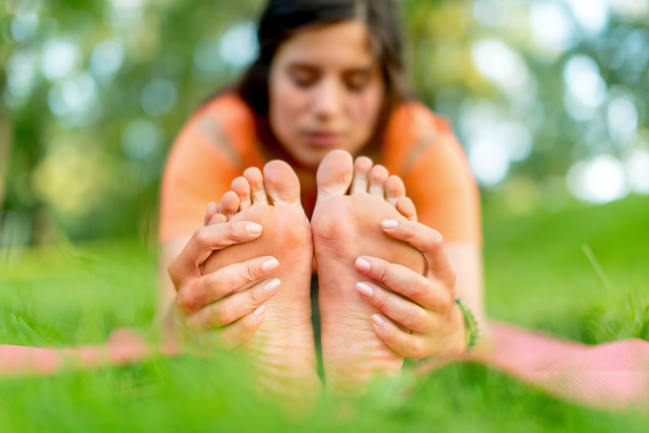 woman stretching holding feet