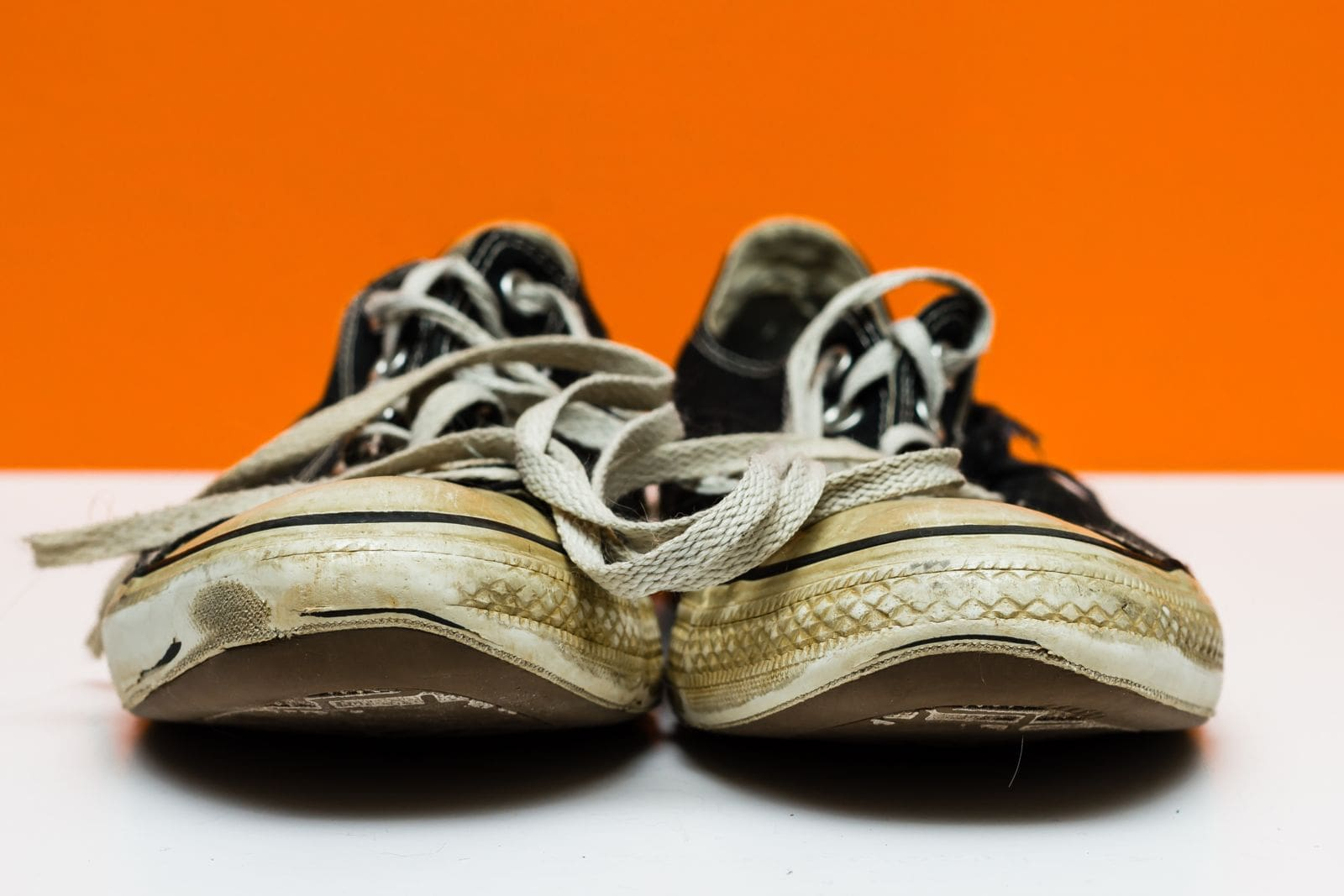 worn out sneakers on orange background