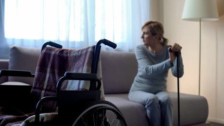 woman with MS cane and wheelchair