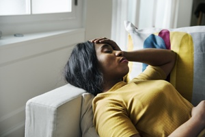 woman with migraine lying down on couch holding head