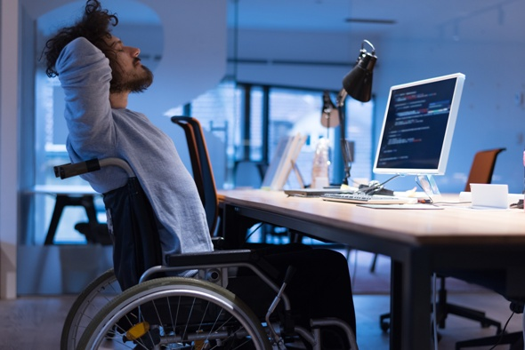 person with MS in wheelchair working at a computer