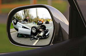 looking back at a car wreck with the side view mirror