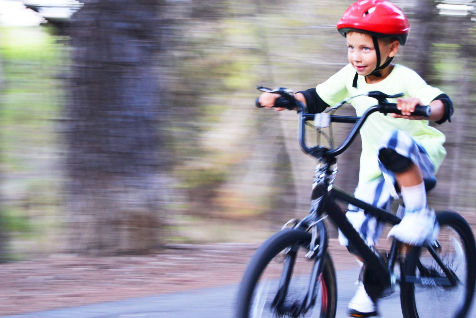 Child With Red Helmet Riding a Bicycle