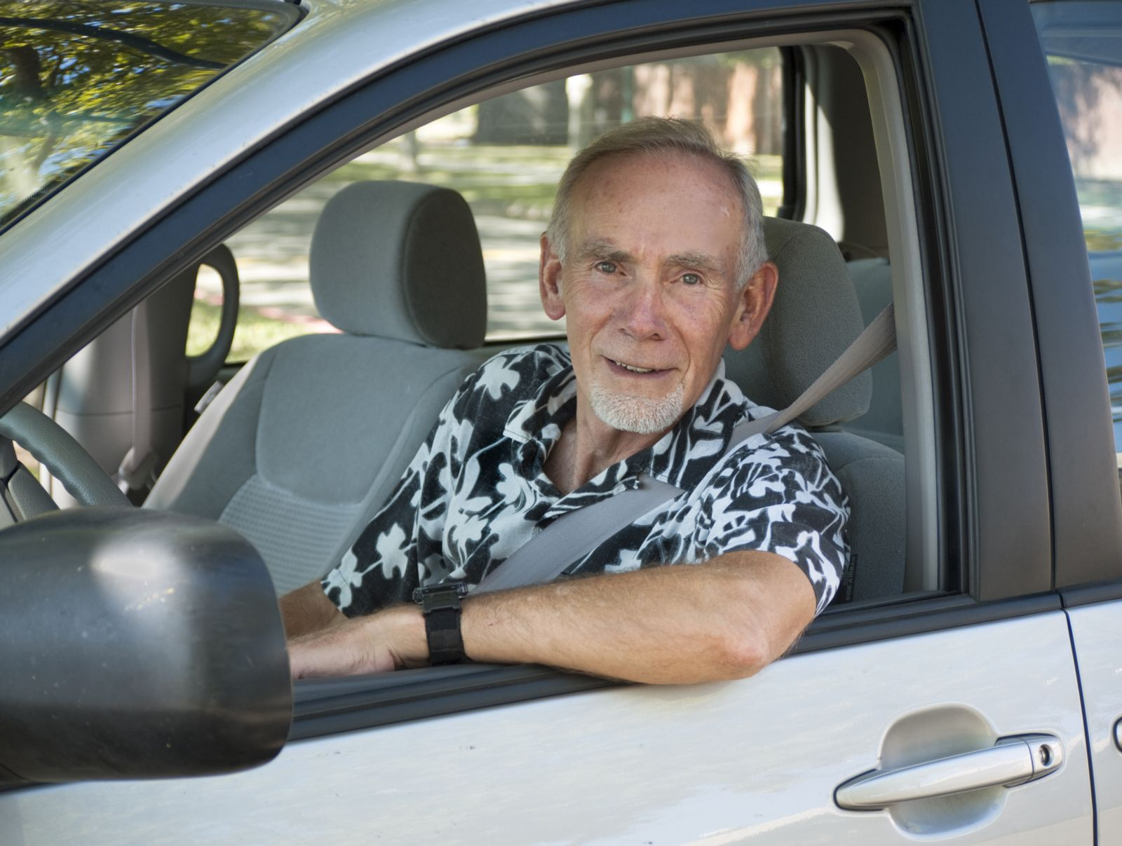 Elderly Man Sitting in Vehicle