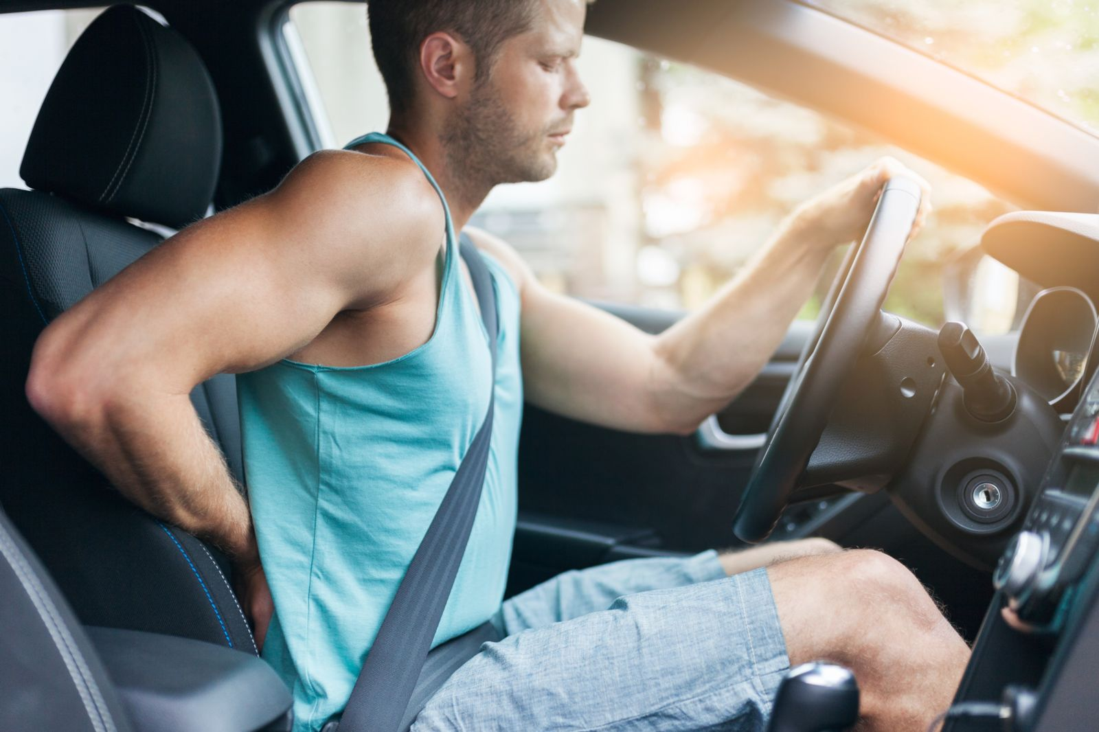 Man Driving and Rubbing His Back