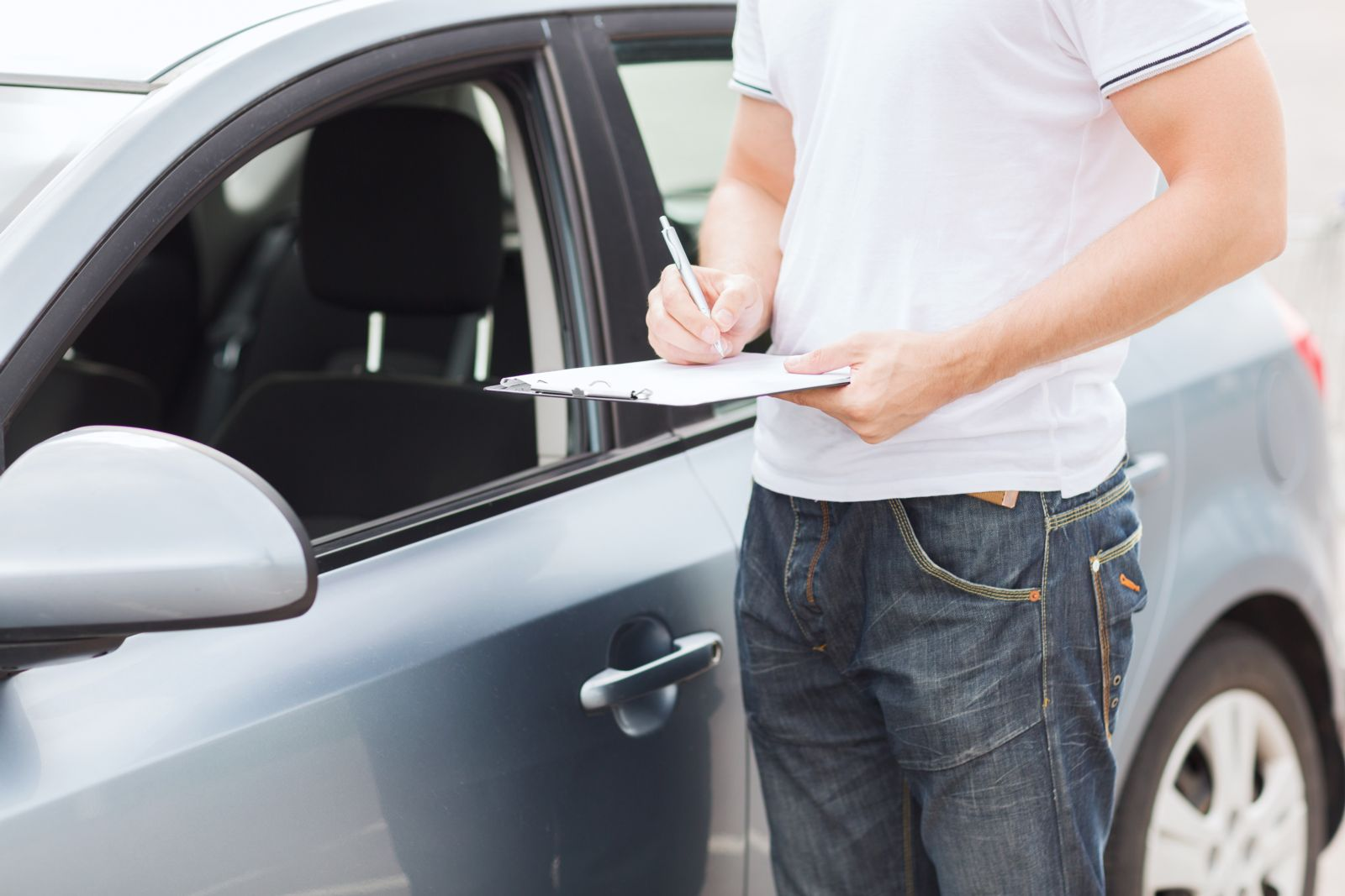 Man Holding Clipboard Outside of Car